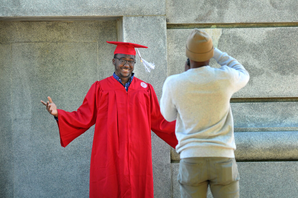 A graduating senior poses for photos at the base of the Belltower.