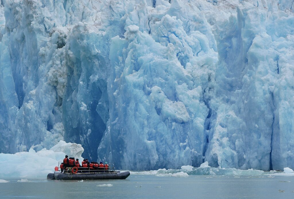 Zodiac full of travelers cruises past a glacier.