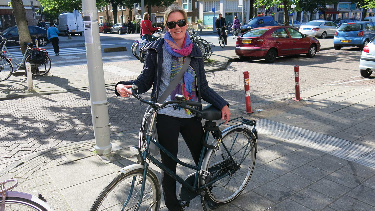 Jennifer Tooles poses with a bike on a busy street in Amsterdam.