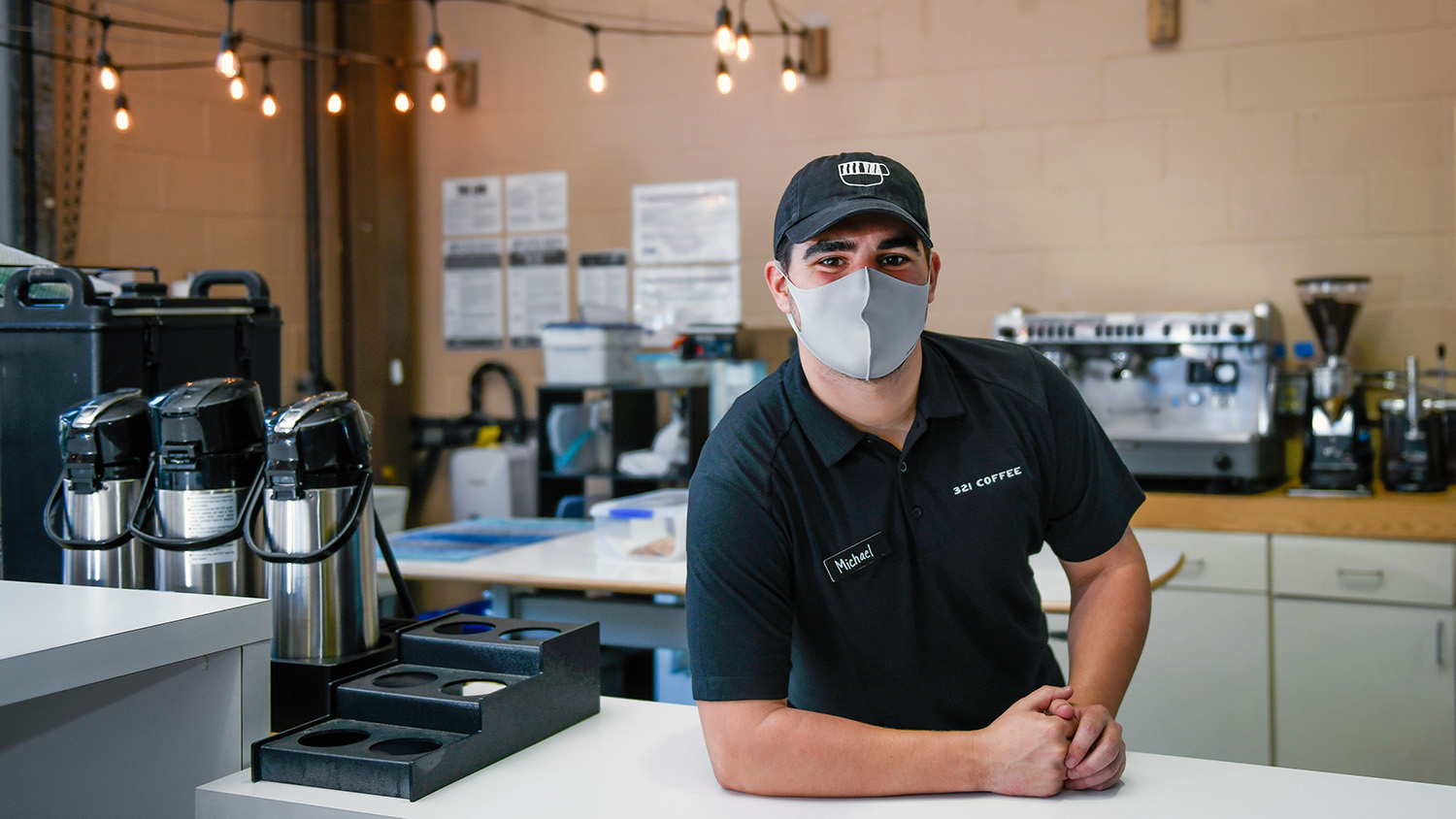 Michael Evans stands behind the counter of 321 Coffee for a portrait.