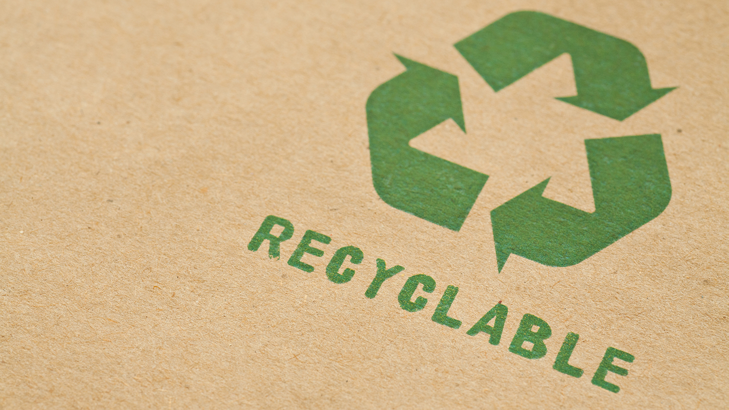 Green recycle symbol on cardboard