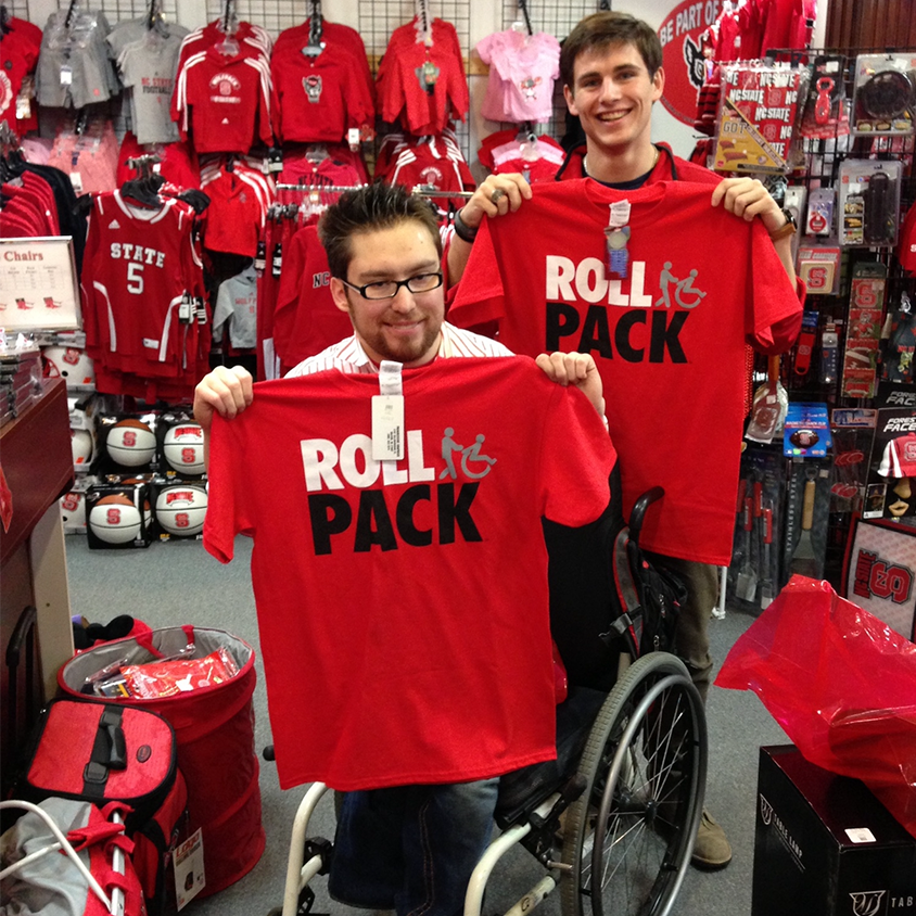 Will Privette and Andy Walsh inside Wolfpack Outfitters holding RollPack t-shirts.