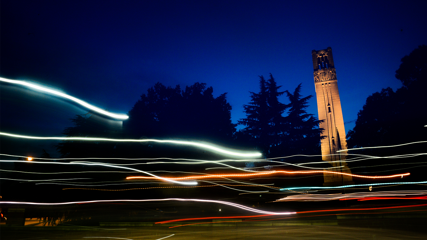 The Belltower at night, with lights from passing cars in the foreground.